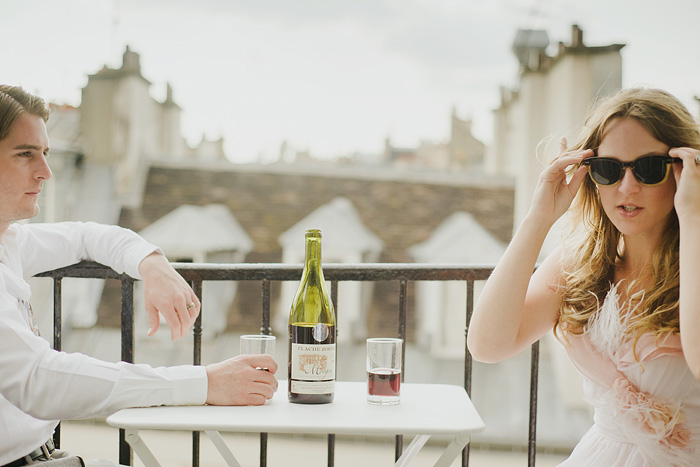 Destination Paris elopement - Newlyweds drinking wine on balcony