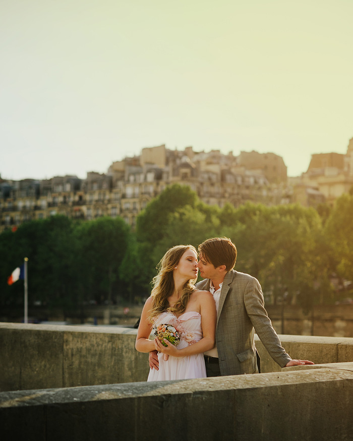 Paris elopement photographer - Newlyweds kissing by French flag