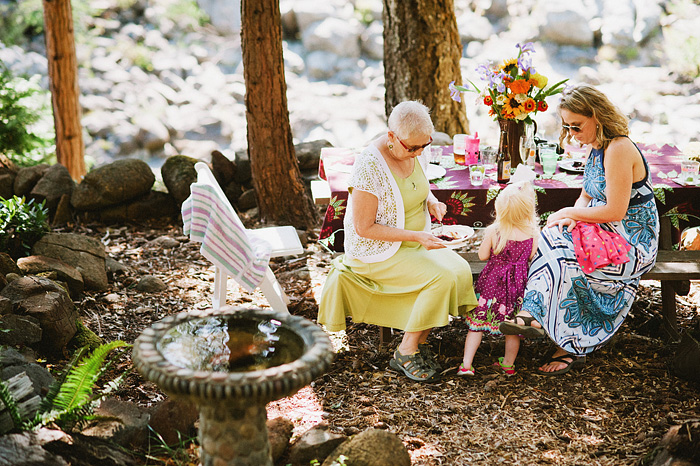 Guests sitting at a picnic table near the Smith River - Intimate Backyard Wedding - Gasquet, CA