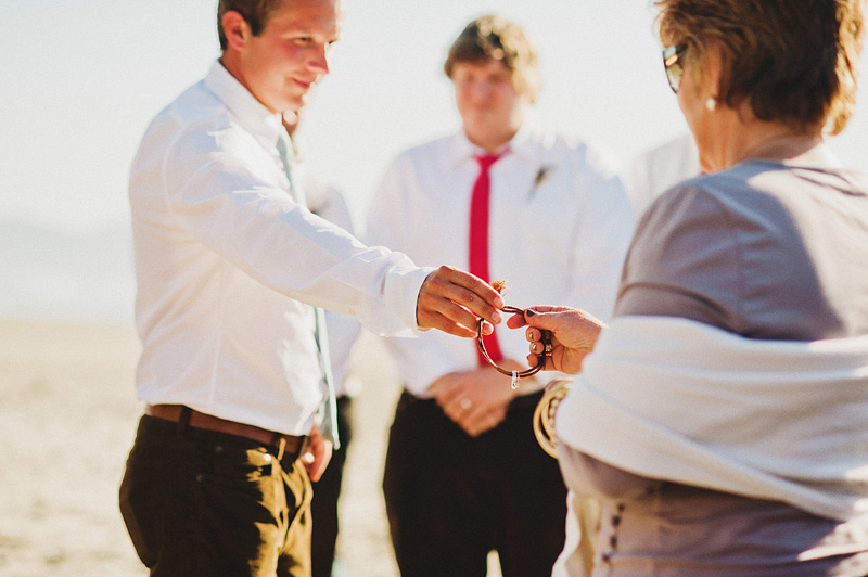 Tillamook Wedding Photographer - Groom's brother passing rings to Mother of the Groom for a blessing - Oceanside Beach Ceremony