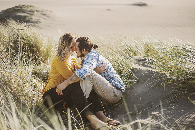 Humboldt Portrait Photographer - Kissing while hiding from the wind at Mad River Beach, Arcata, CA