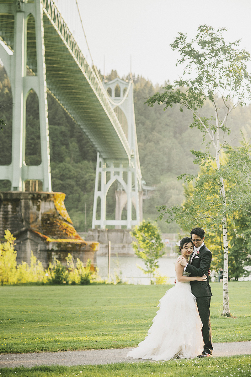 Oregon Wedding Photographer - Bride and Groom embracing under the St. John's Bridge in Cathedral Park