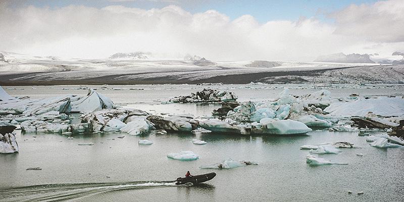 Iceland Wedding Photographer - Man in a boat herding icebergs in Jökulsárlón