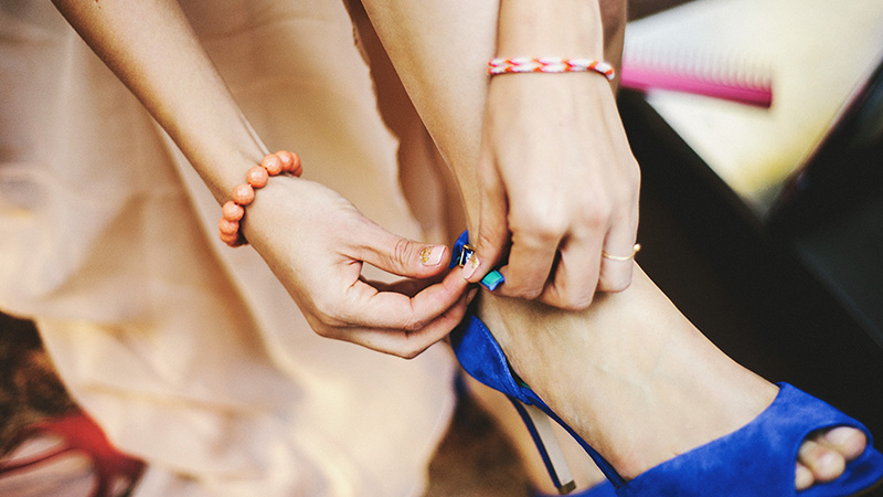 Bride strapping on her blue heels | Kate & Will's Camp Seely Wedding | Kim Smith-Miller