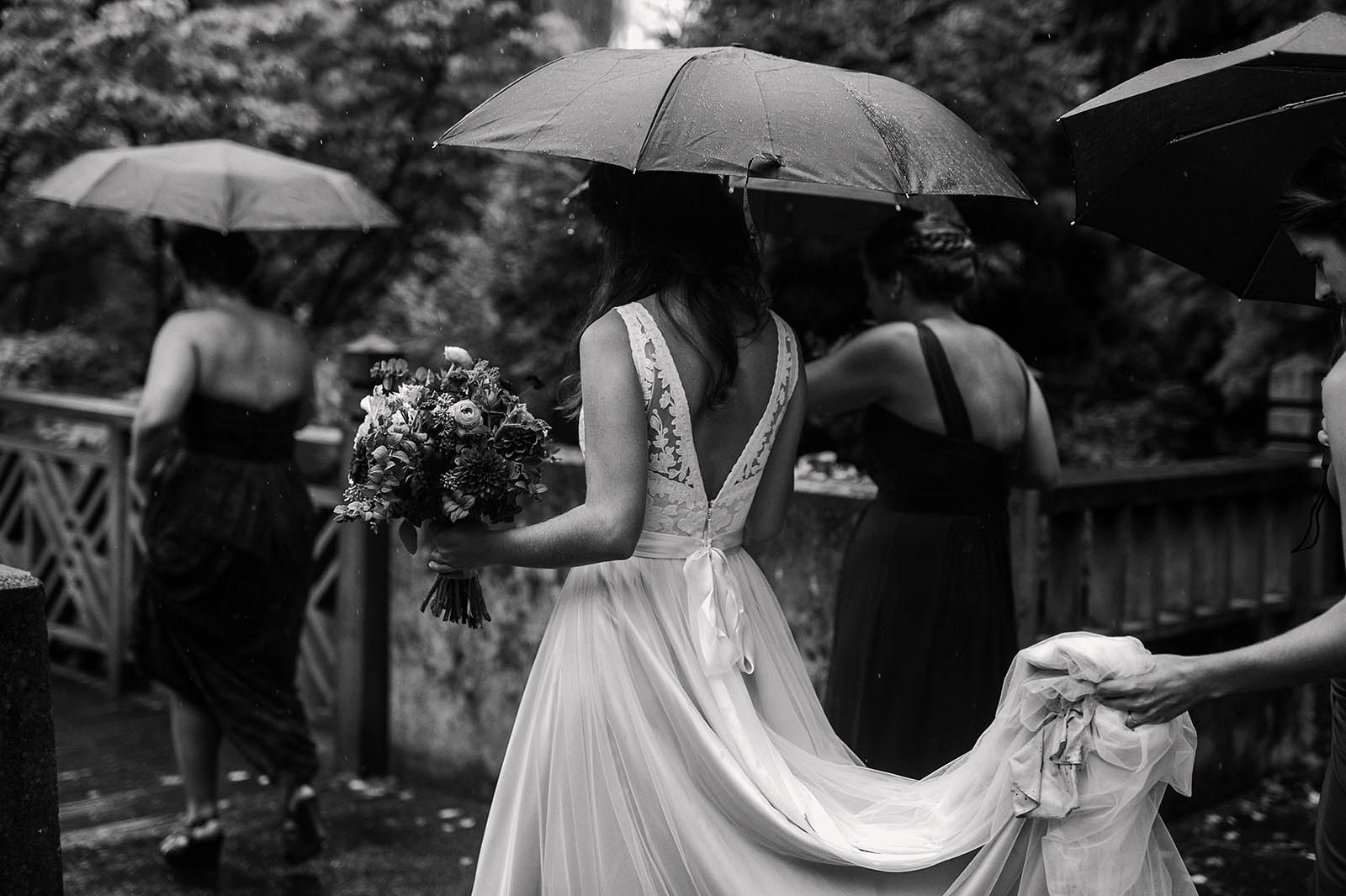 Mother of Bride holding dress during rainy ceremony at Crystal Springs Rhododendron Garden