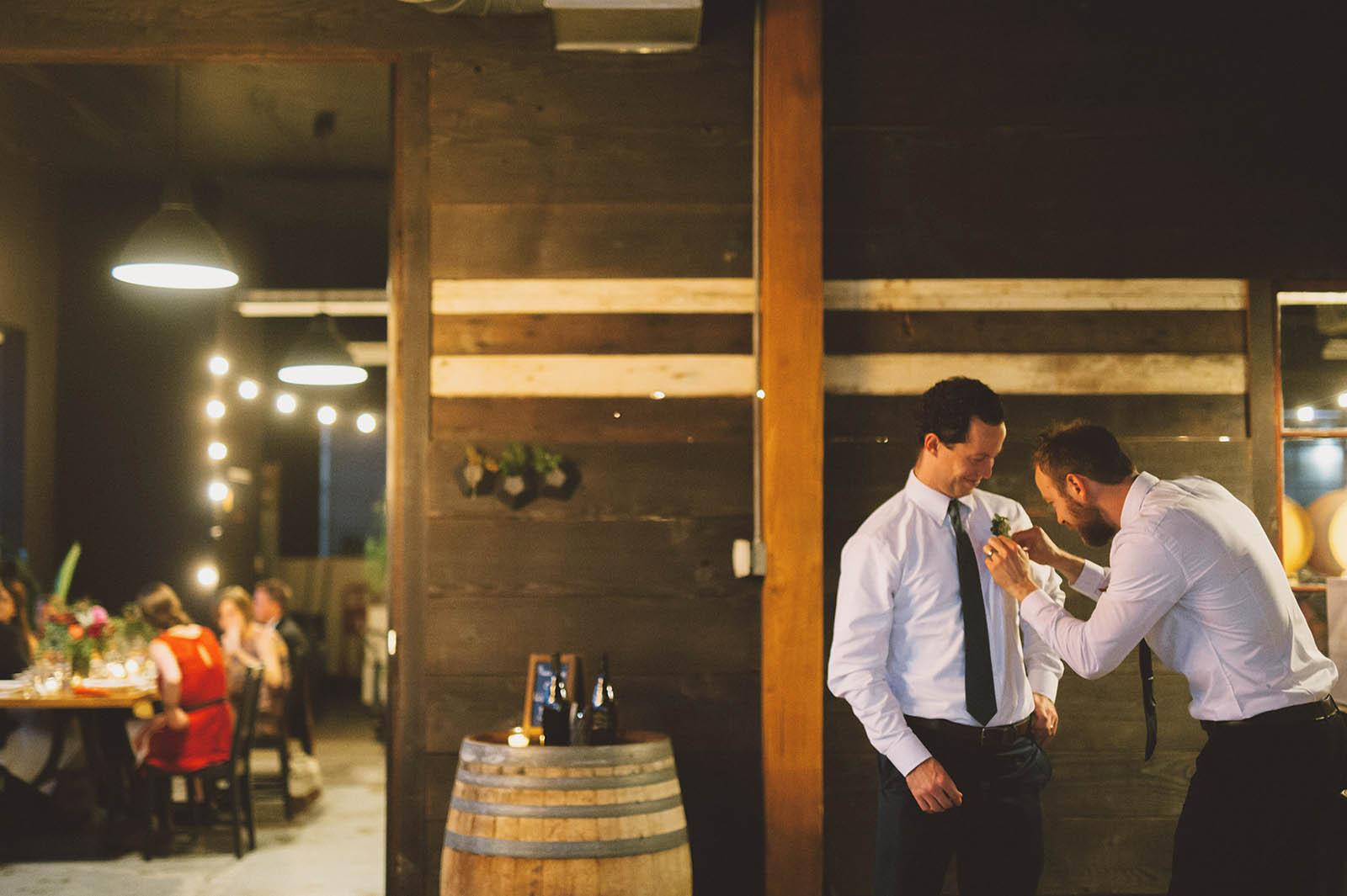 Groomsmen adjusting their boutonnieres | Clay Pigeon Winery Wedding