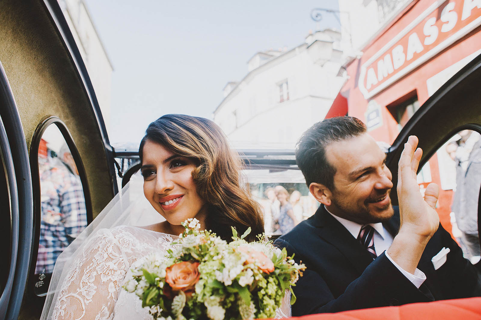 Bride and Groom waving at crowds of tourists in the street | Springtime Paris Elopement at Parc des Buttes Chaumont