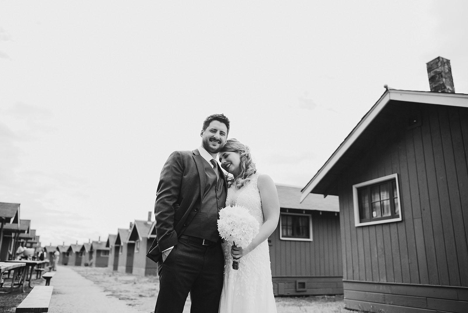 Bride and Groom posing near the cabins at Cama Beach State Park | Camano Island Wedding