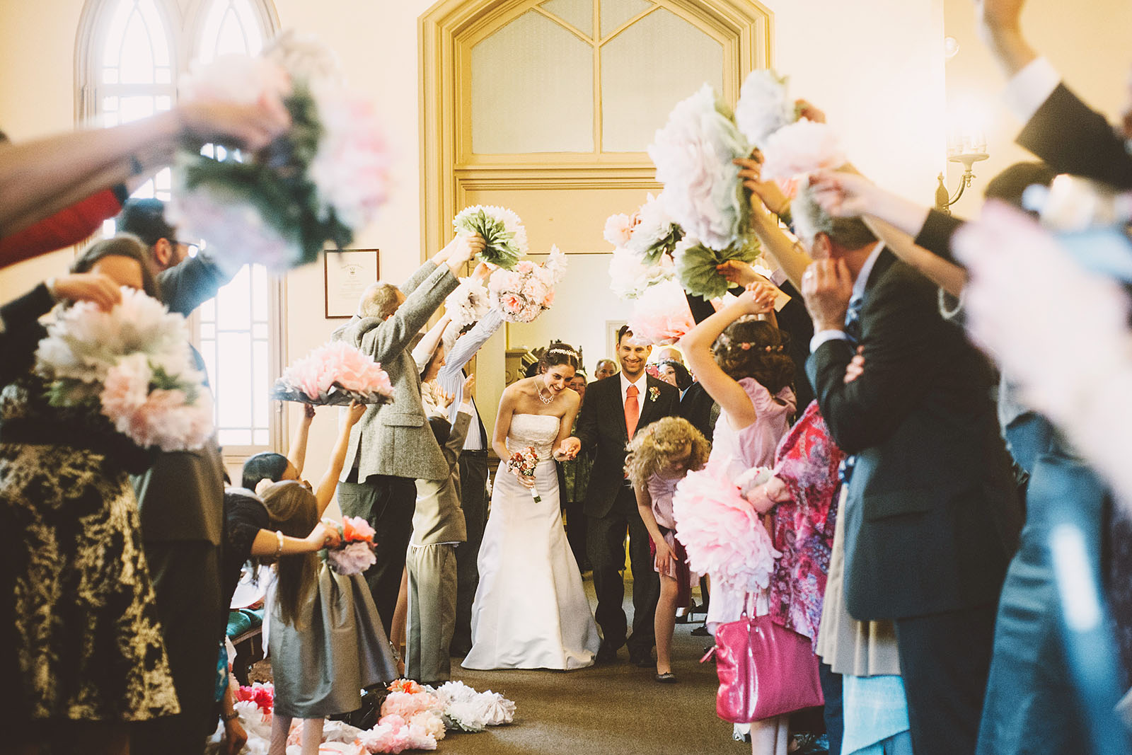 Bride and Groom's grand exit under paper flowers | Old Church Wedding Photos