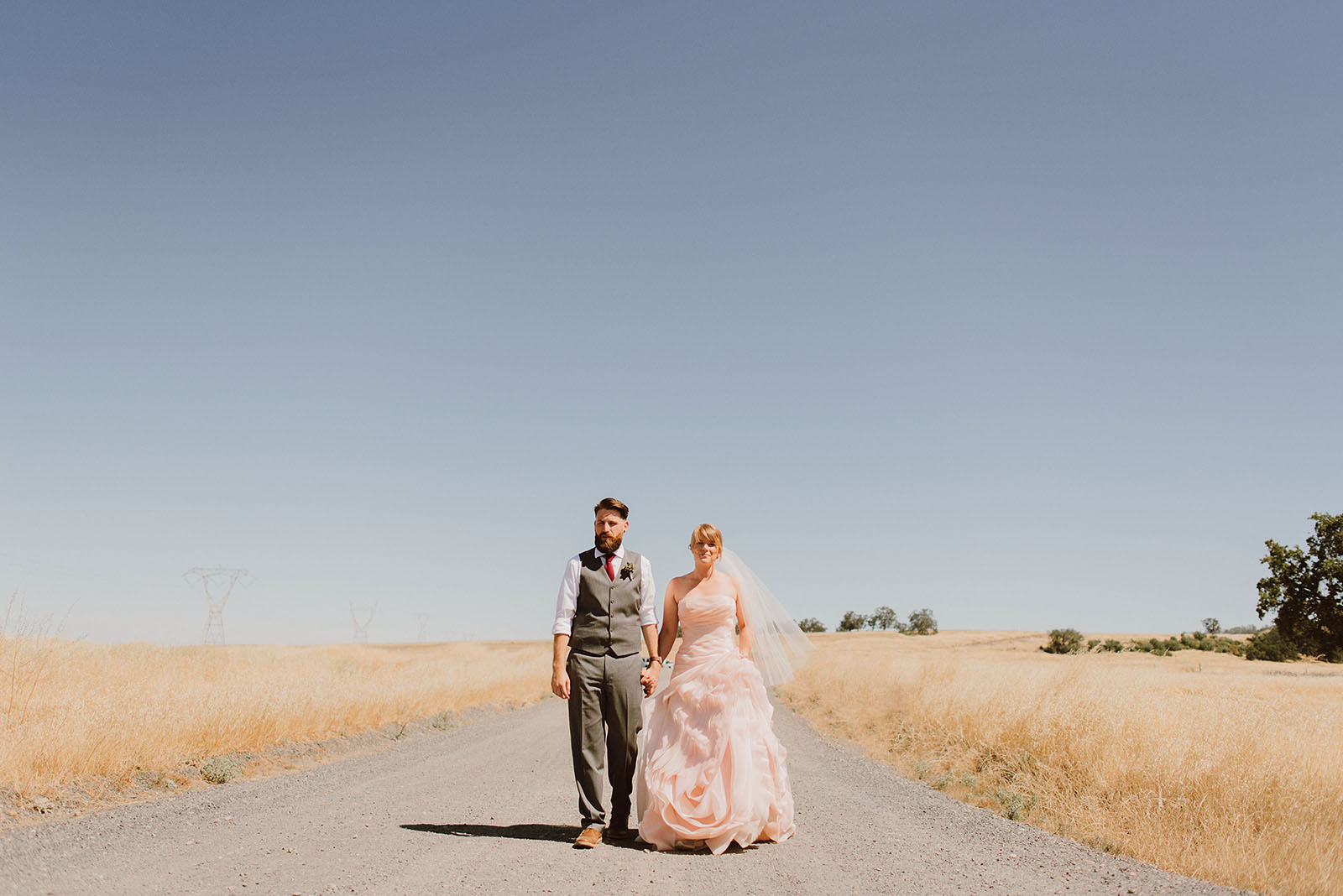 Bride and Groom walking down a road in Upper Bidwell Park | Backyard Chico California Wedding