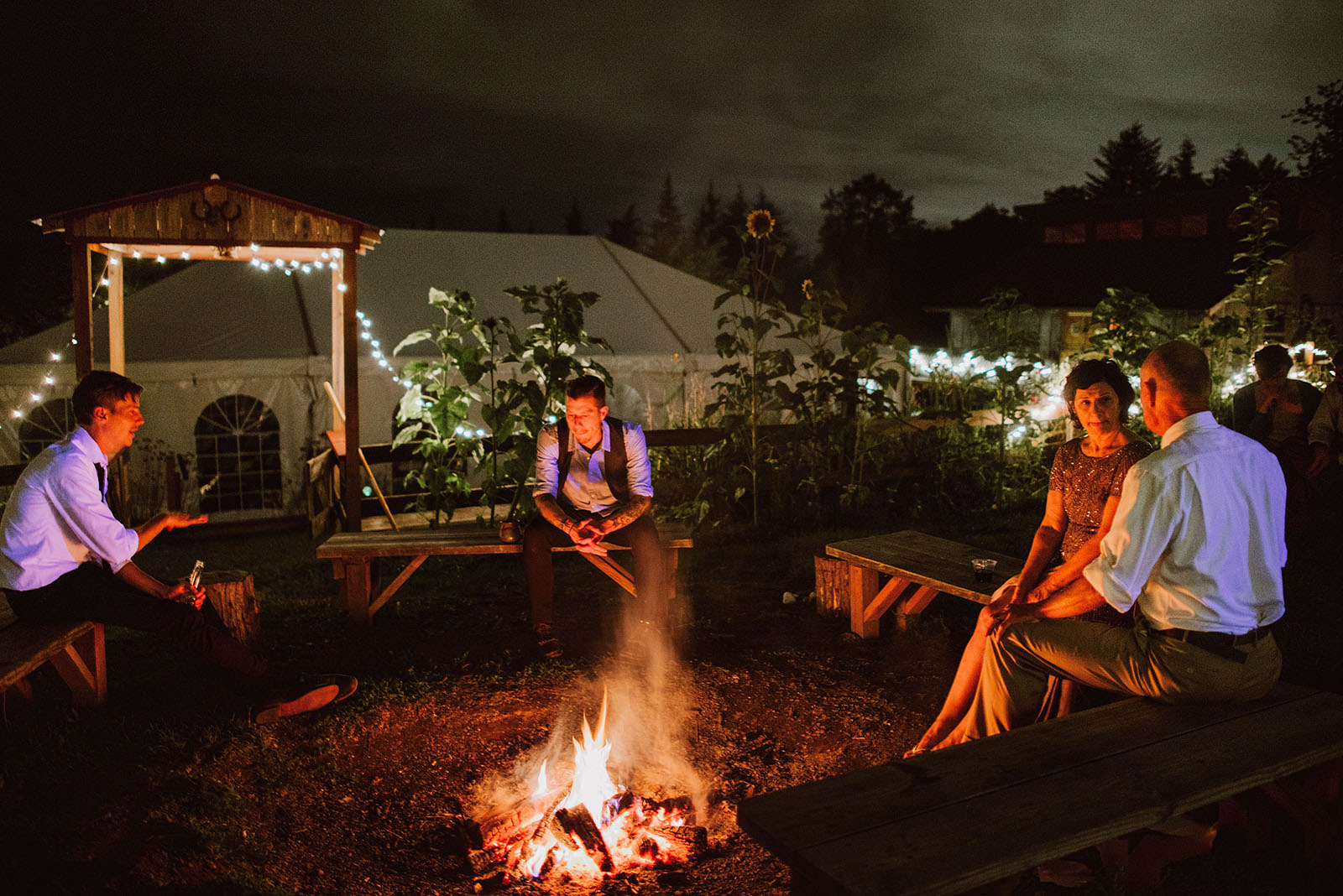 Guests huddled around the pit fire at Pendarvis Farm | Woodsy Campground Wedding