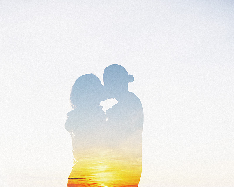 Double exposures in Photoshop - Couple Kissing overlayed on a sunset