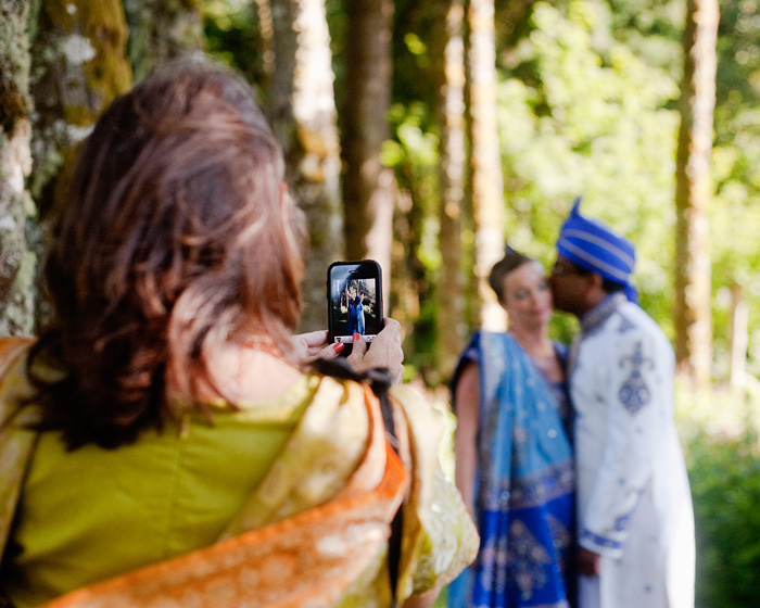 Female Guest in Sari takes iPhone photo of Bride and Groom - Bridal Veil Lakes wedding - Portland Oregon