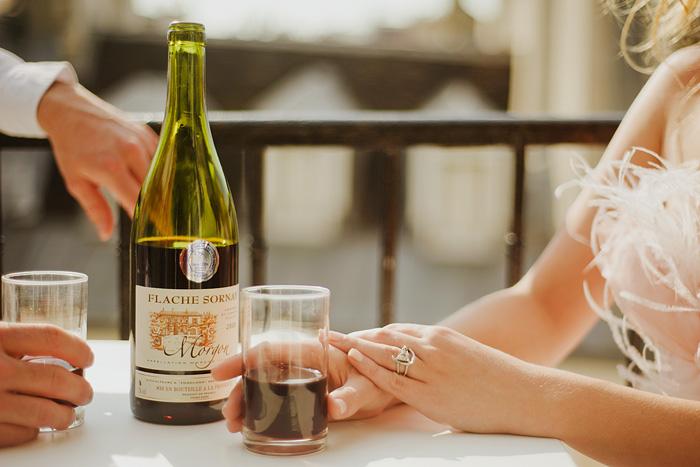 Destination Paris Elopement - Bride drinking wine on balcony