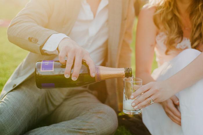Groom Pouring Champagne in Champ de Mars - Paris elopement