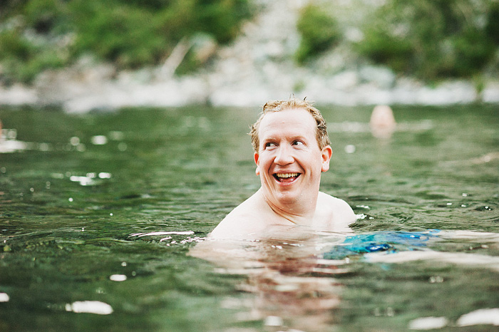 Groom smiling while swimming in the Smith River - Intimate Backyard Wedding - Gasquet, CA
