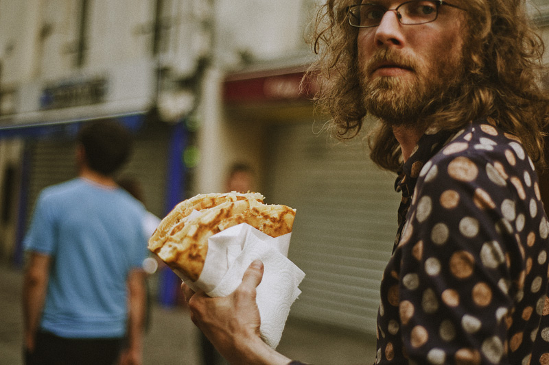 Paris wedding photographer - Brett holding crepes on Rue Saint-Denis