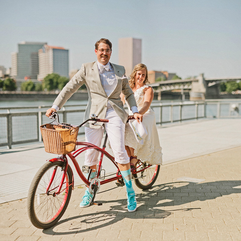 Multnomah Courthouse Wedding Photographer - Bride and Groom posing on tandem bicycle - Bokeh Panorama - Portland Bike Parade Wedding
