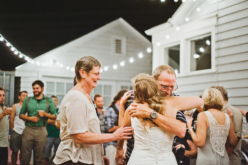 Multnomah Courthouse Wedding Photographer - Mother and Father of Groom hugging the bride after champagne toasts - Backyard Reception