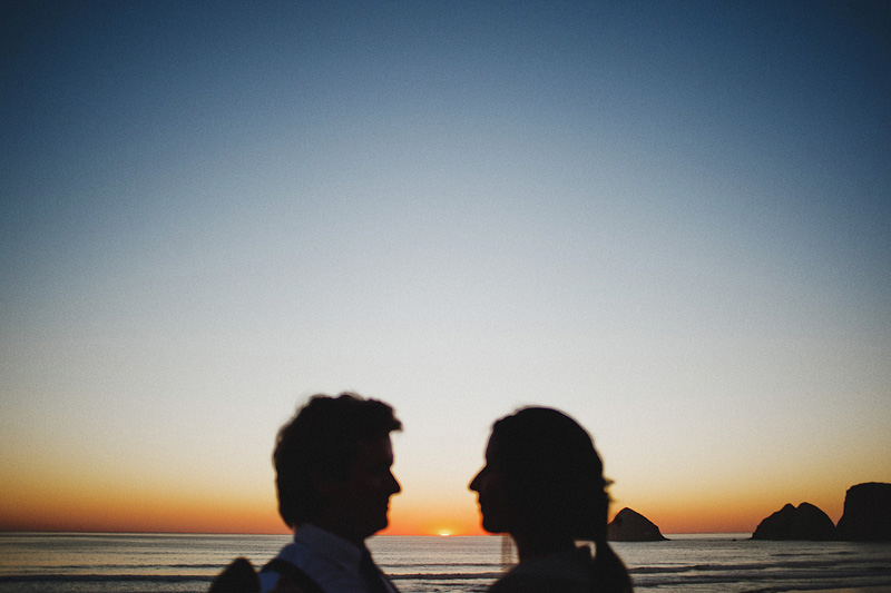 Tillamook Wedding Photographer - Bride and Groom watch the sun set over the ocean