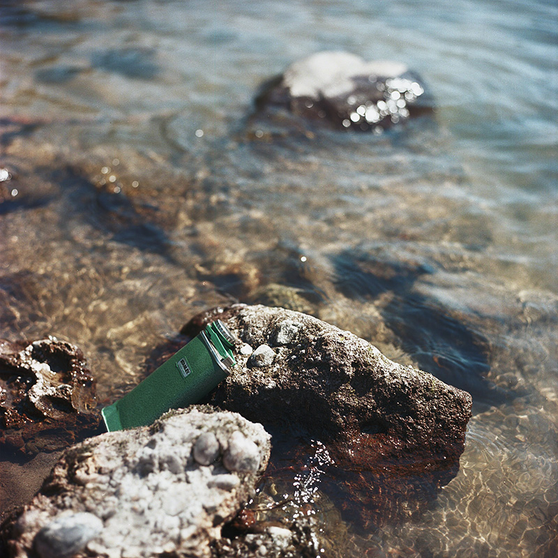 Portland Film Photographer - Flask of Cascade Mountain Gin sitting on the shore of Sandy River - Rolleiflex