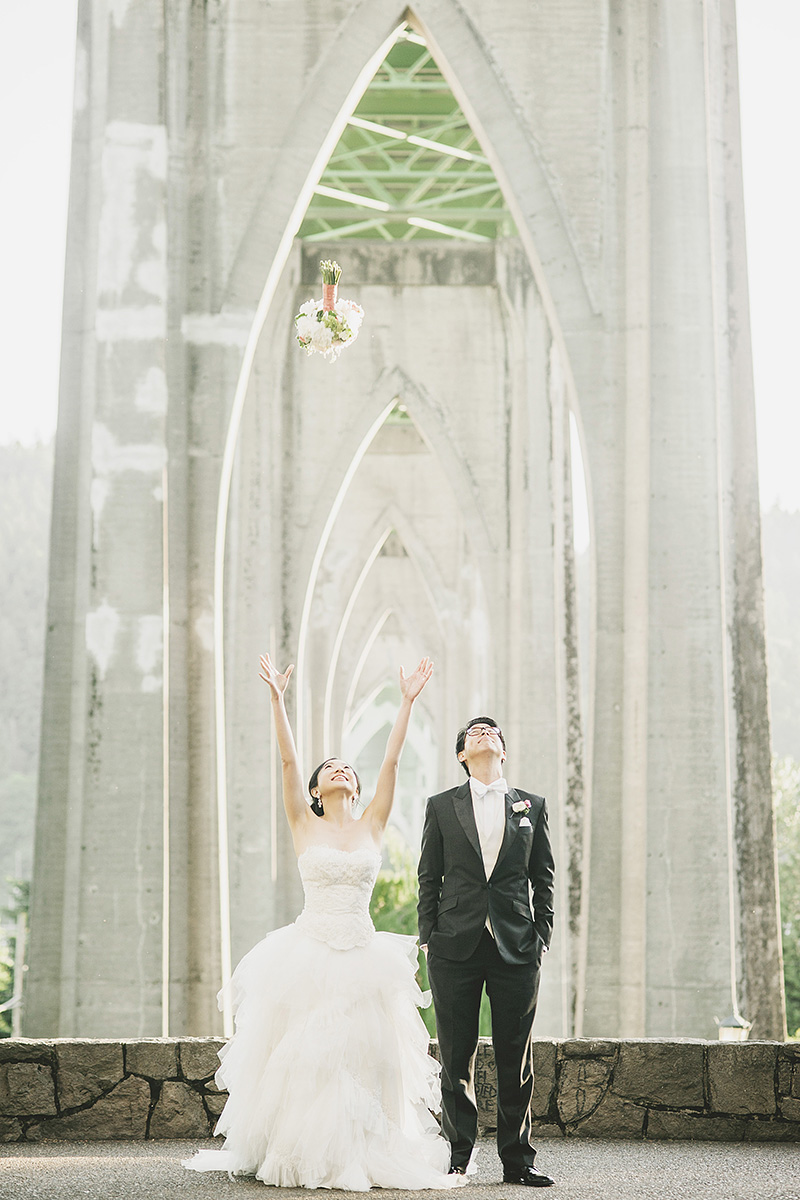 Oregon Wedding Photographer - Bride tossing bouquet under the St. John's Bridge in Cathedral Park
