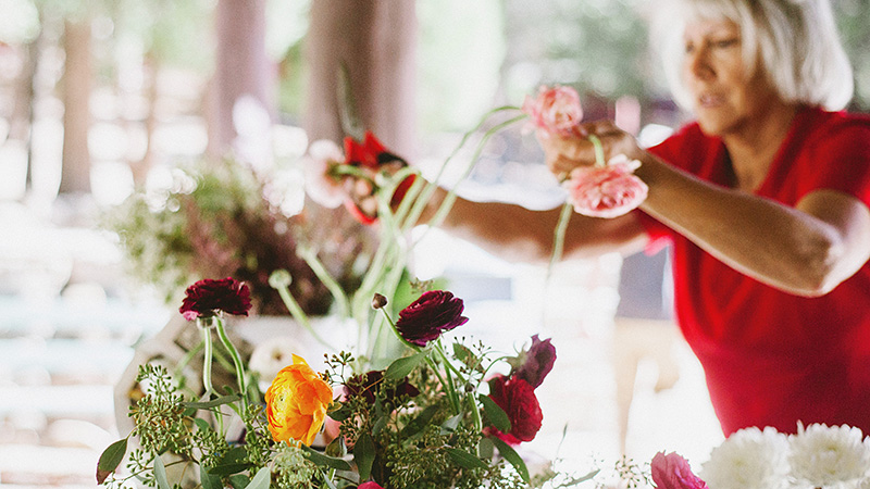 Bride's grandmother arranging flowers | Kate & Will's Camp Seely Wedding | Kim Smith-Miller