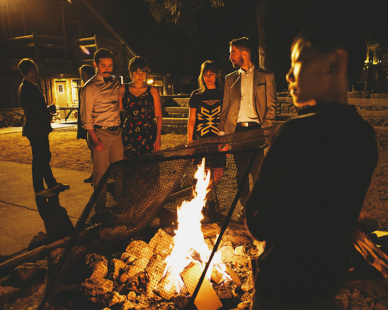 Guests gather around the fire pit at night | Kate & Will's Camp Seely Wedding | Kim Smith-Miller