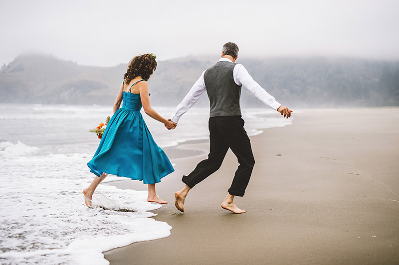 Running away from the ocean tide at Lara and Nate's Camp Westwind wedding