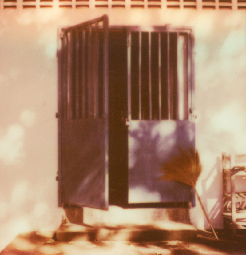 Brooms and an open door at a wat in Thailand | SLR680 Polaroid