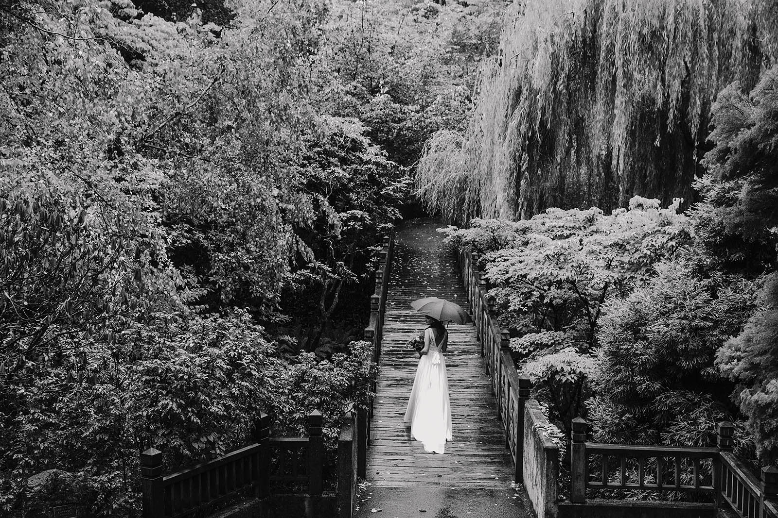 Bride posing on bridge before her Crystal Springs Rhododendron Garden wedding ceremony