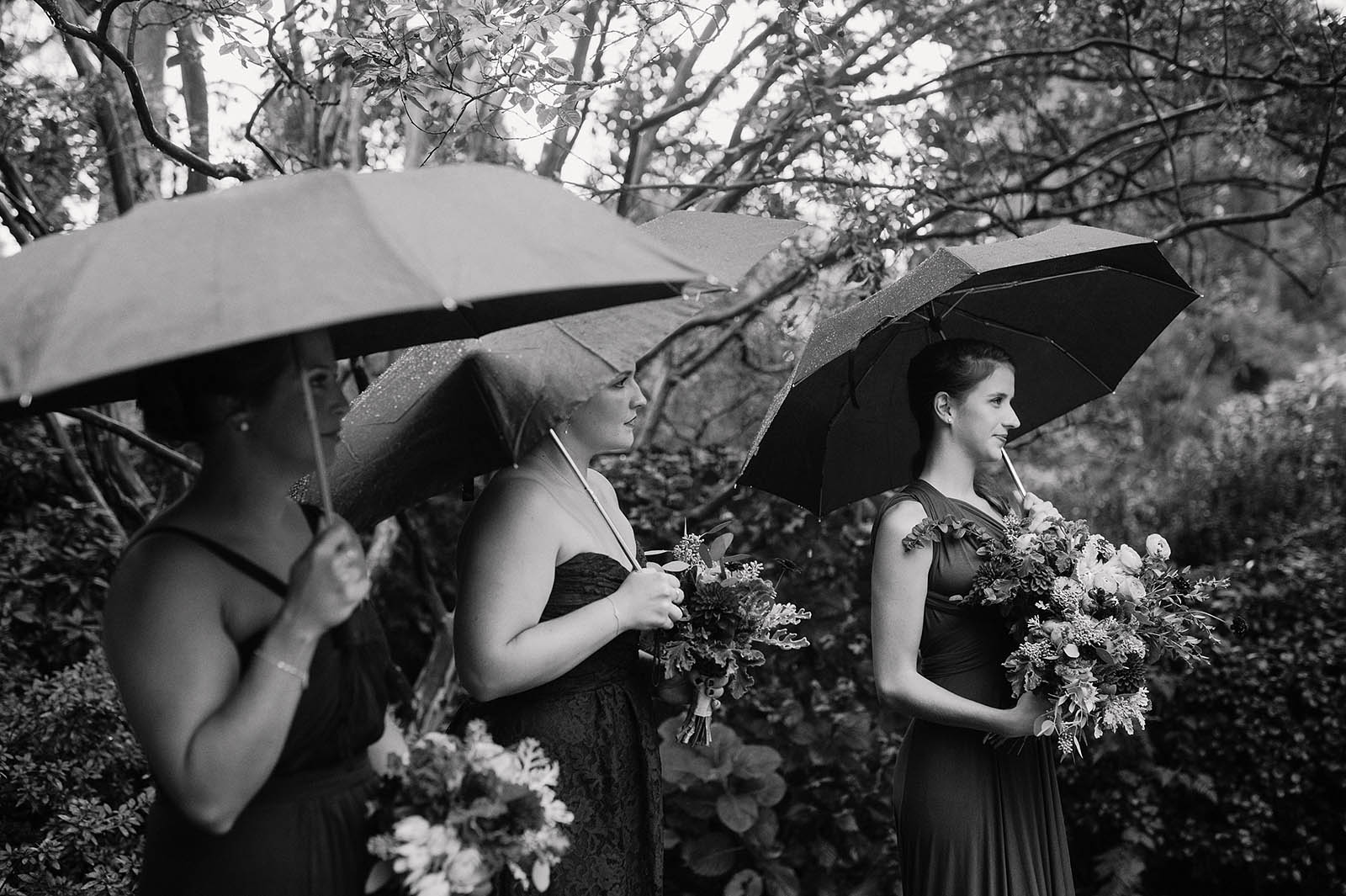 Bridesmaids with umbrellas at a rainy Crystal Springs Rhododendron Garden wedding ceremony
