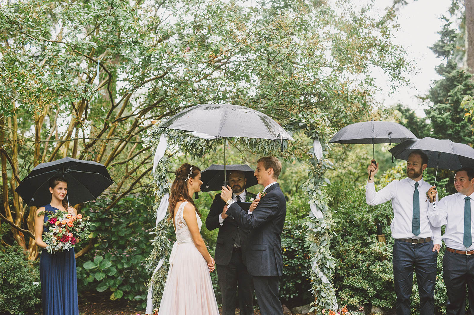 Wedding party holding umbrellas during a rainy Crystal Springs Rhododendron Garden wedding ceremony