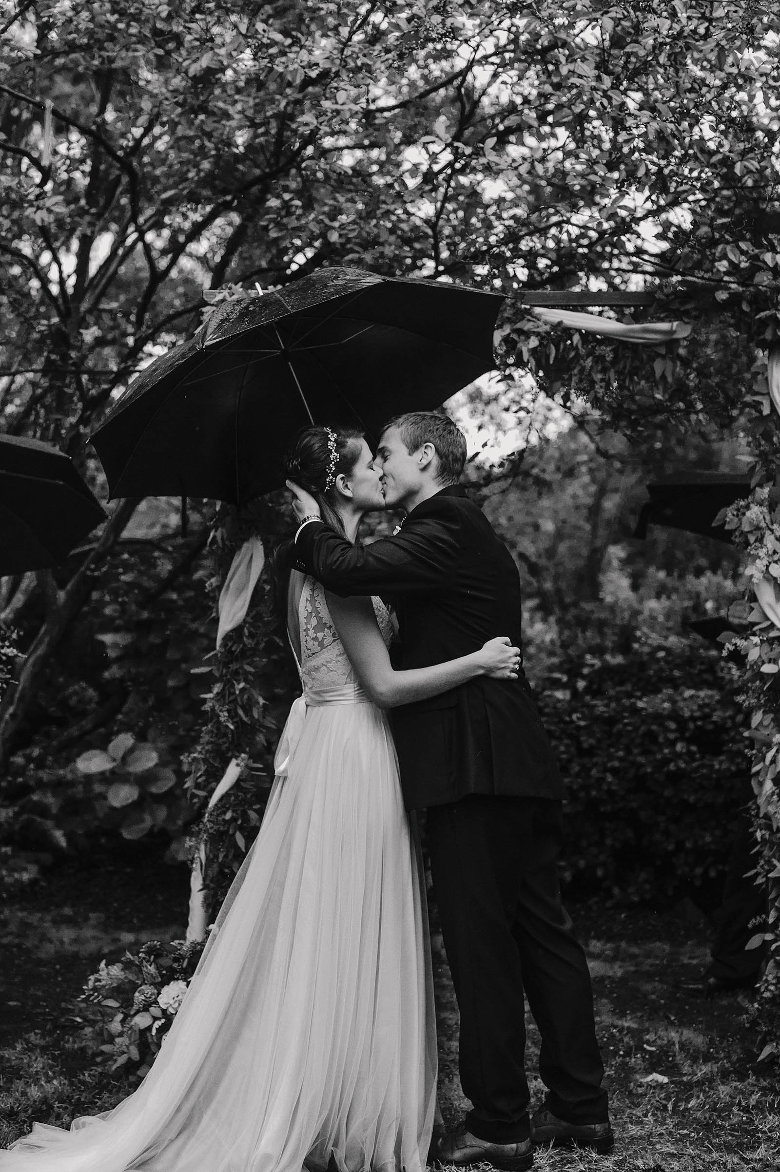Bride and Groom's first kiss under an umbrella | Crystal Springs Rhododendron Garden