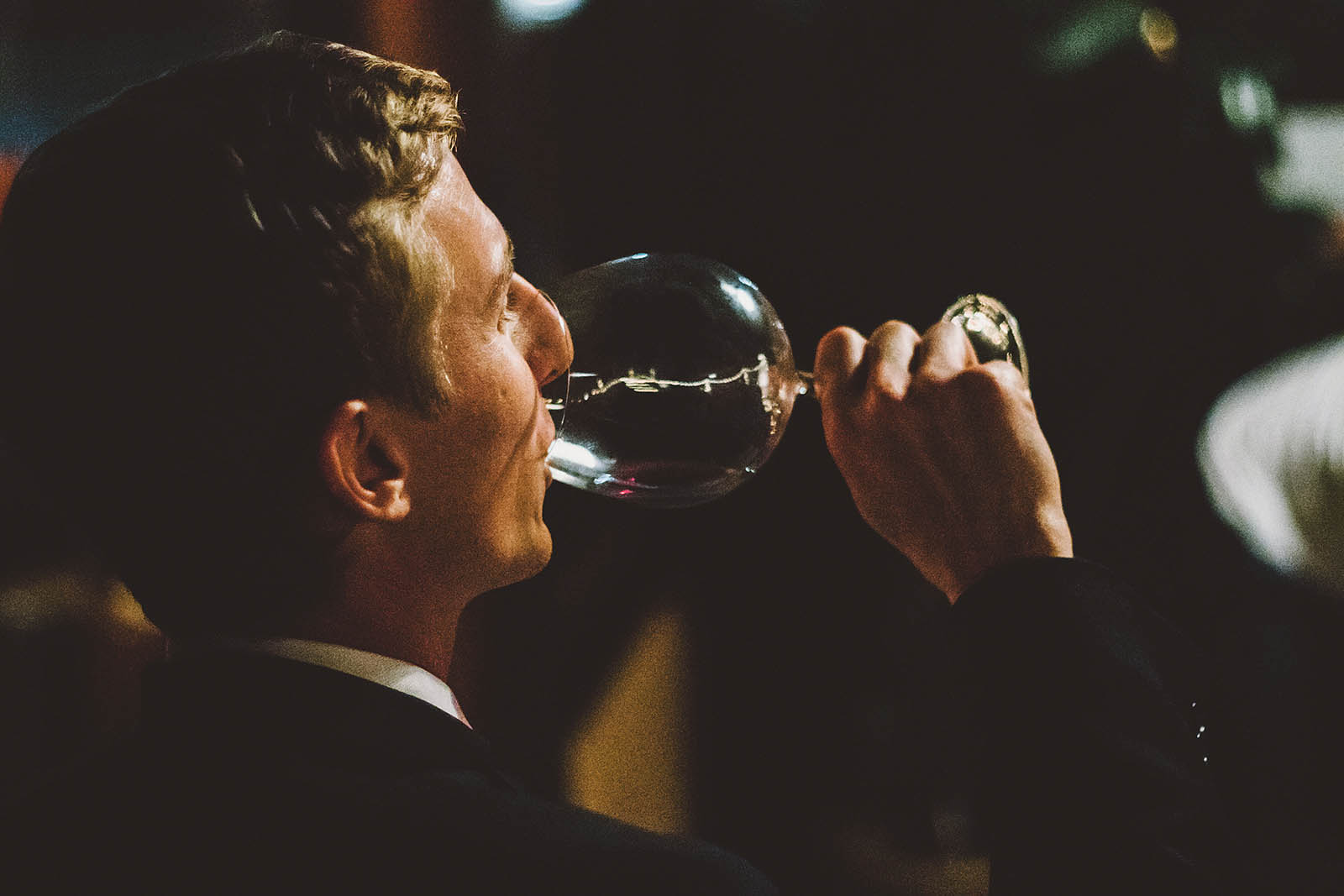 Groom drinking wine at a Clay Pigeon Winery wedding reception
