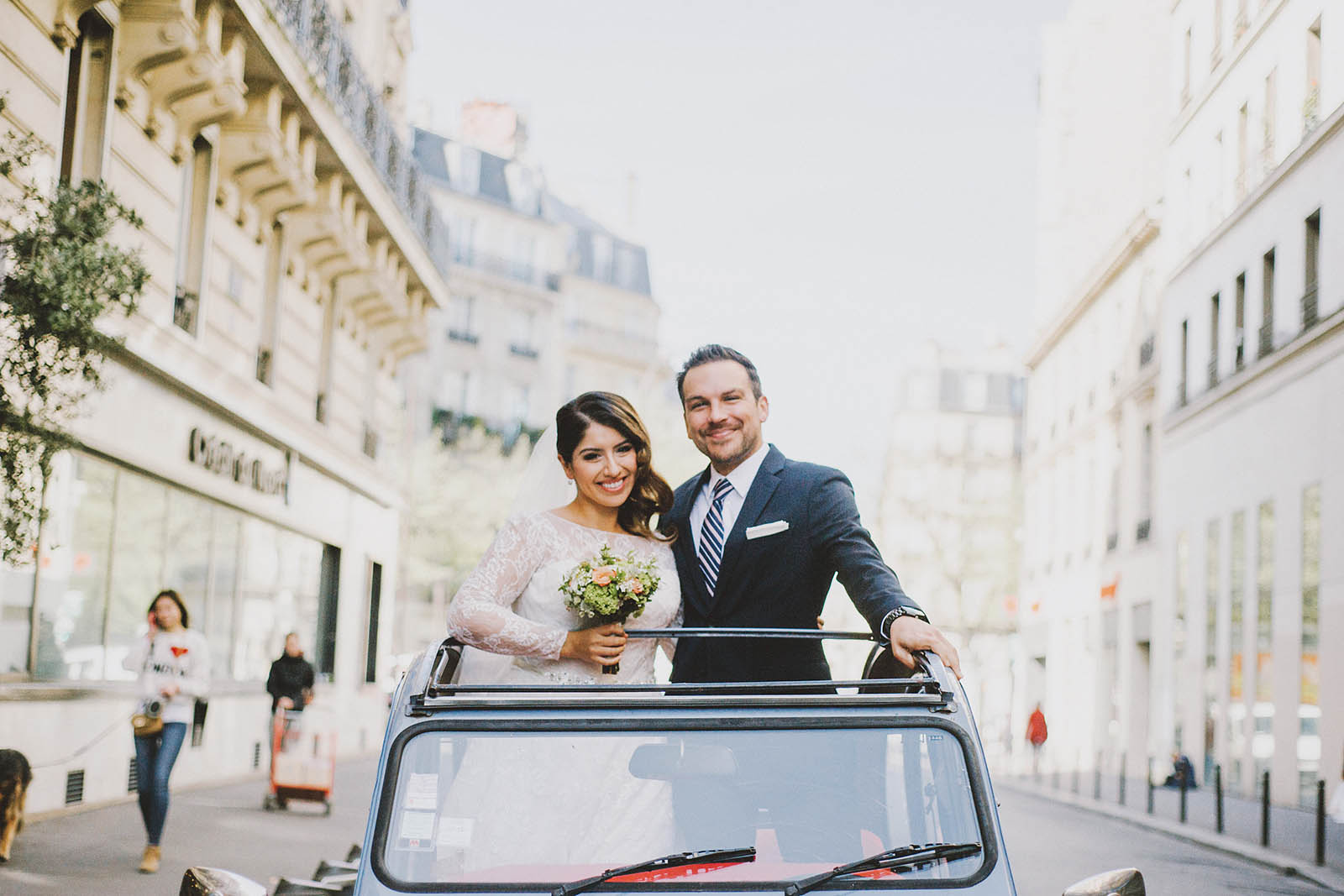 Bride and Groom riding in a 2CV | Springtime Paris Elopement at Parc des Buttes Chaumont