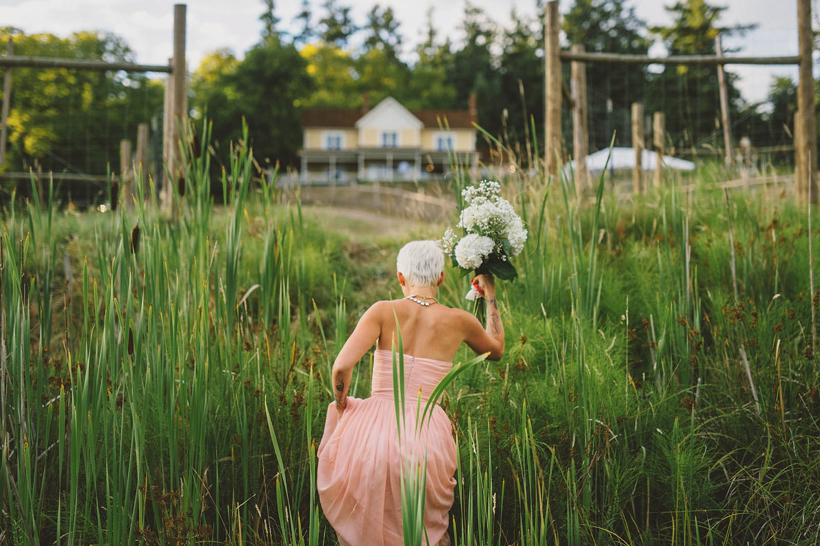 Bride climbing uphill to an Orcas Island wedding reception