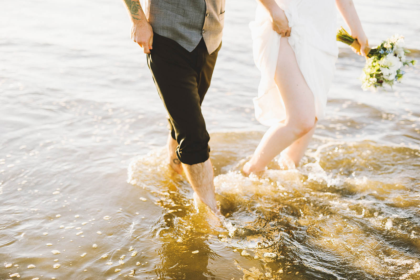 Bride and groom walking barefoot in the ocean | SouWester Lodge Wedding