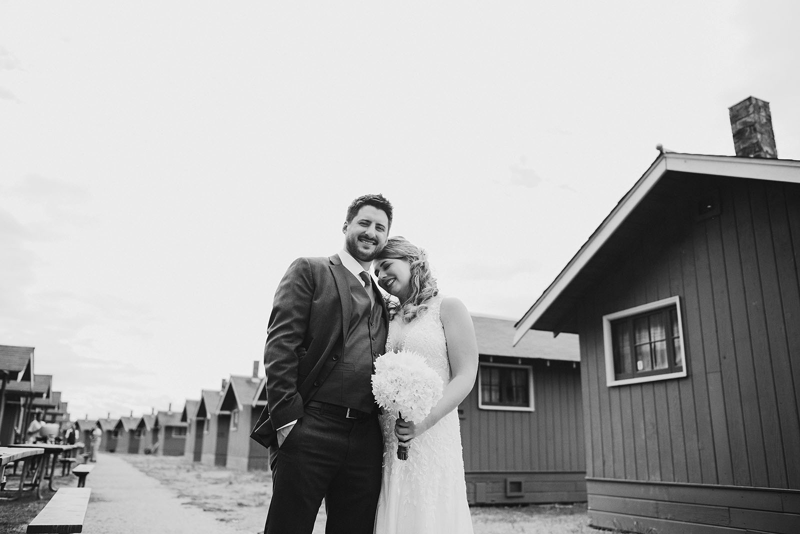 Bride and Groom posing near the cabins at Cama Beach State Park | Camano Island Wedding