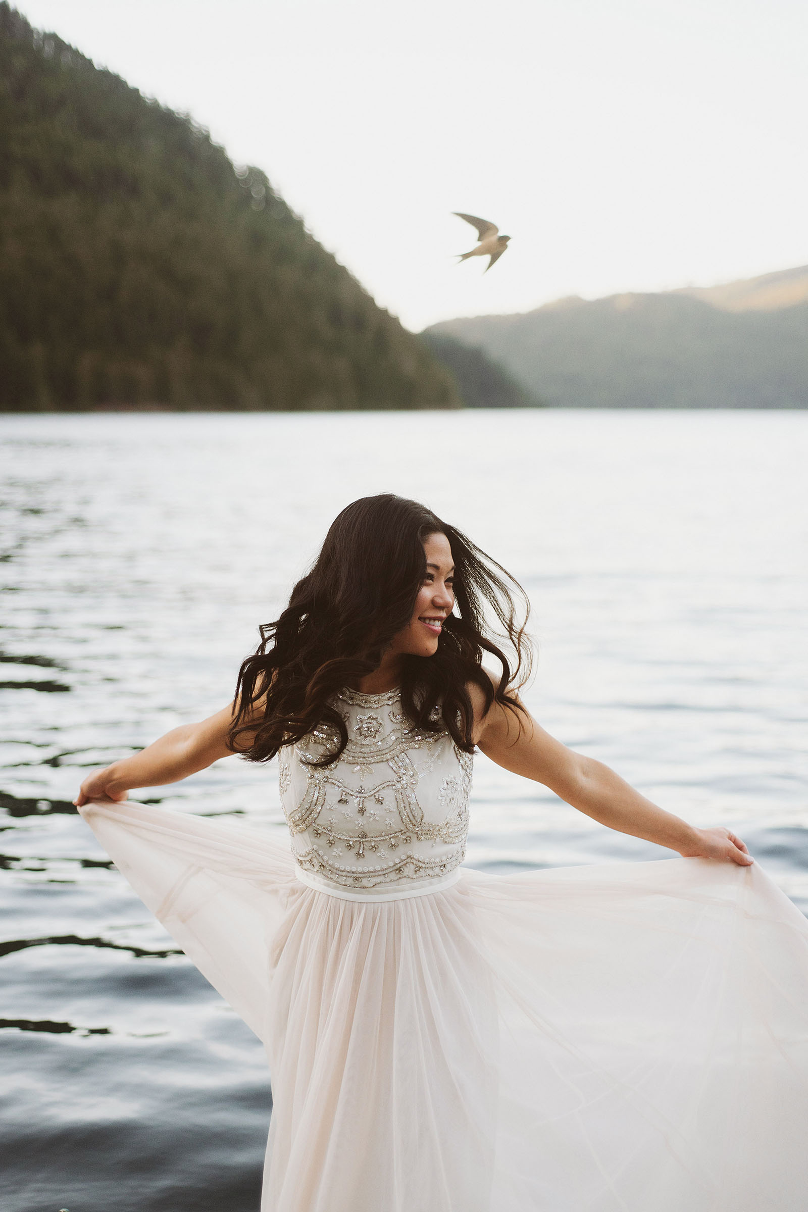 Portrait of bride spinning in her dress as a bird flies overhead | Olympic National Park Wedding