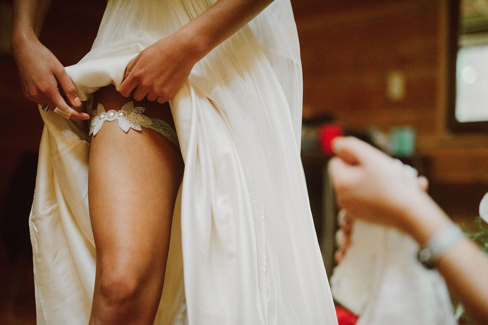 Bride putting on garter for her Camp Namanu wedding