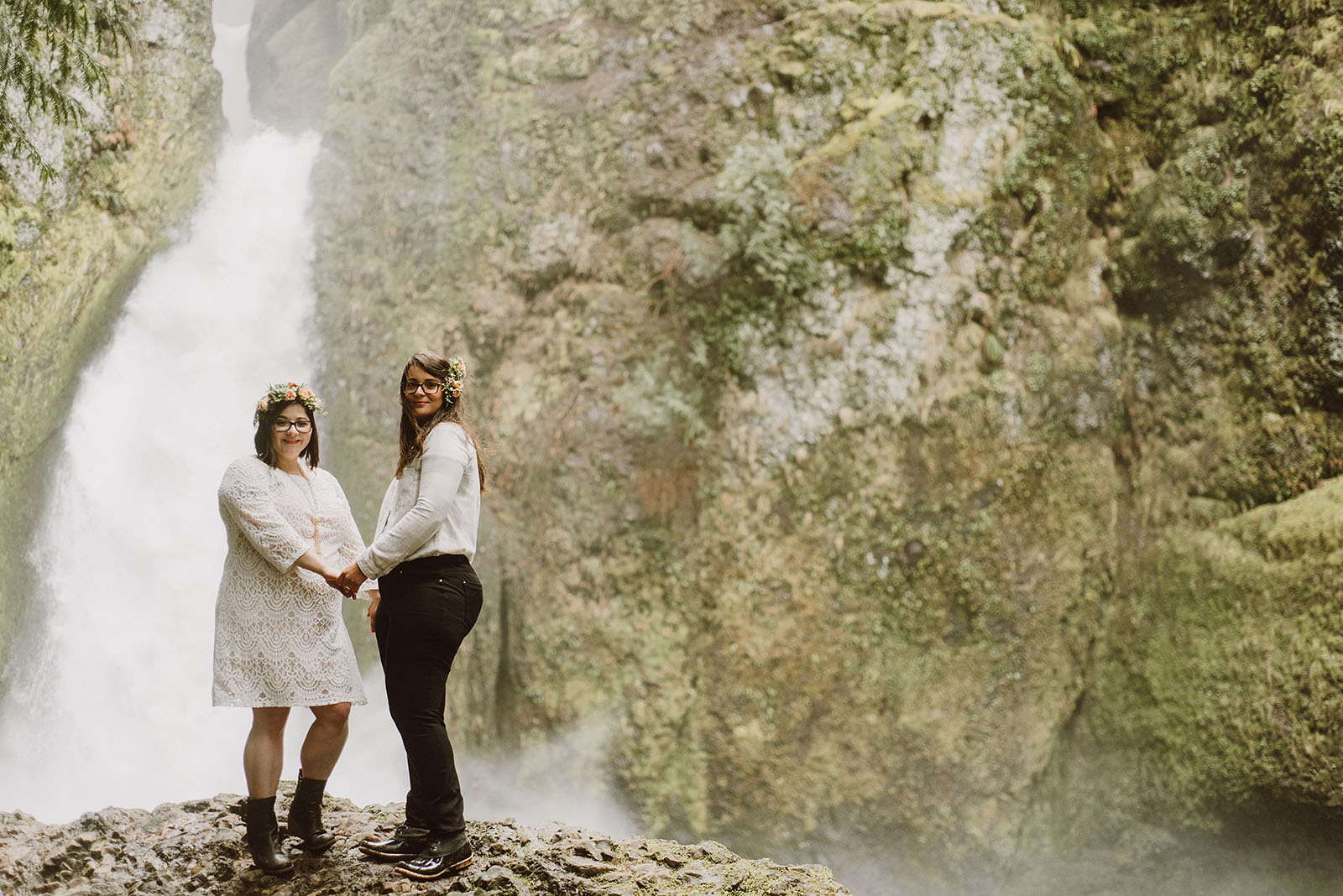 brides holding hands in front of Wahclella Falls - Portland Wedding photography