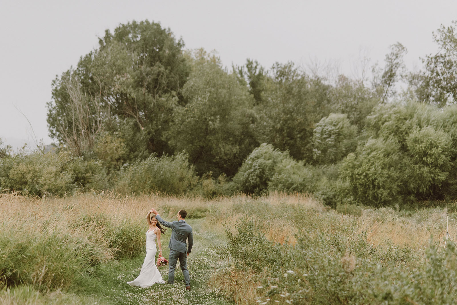 bride and groom dancing in a field on Sauvie Island - Portland Wedding photography