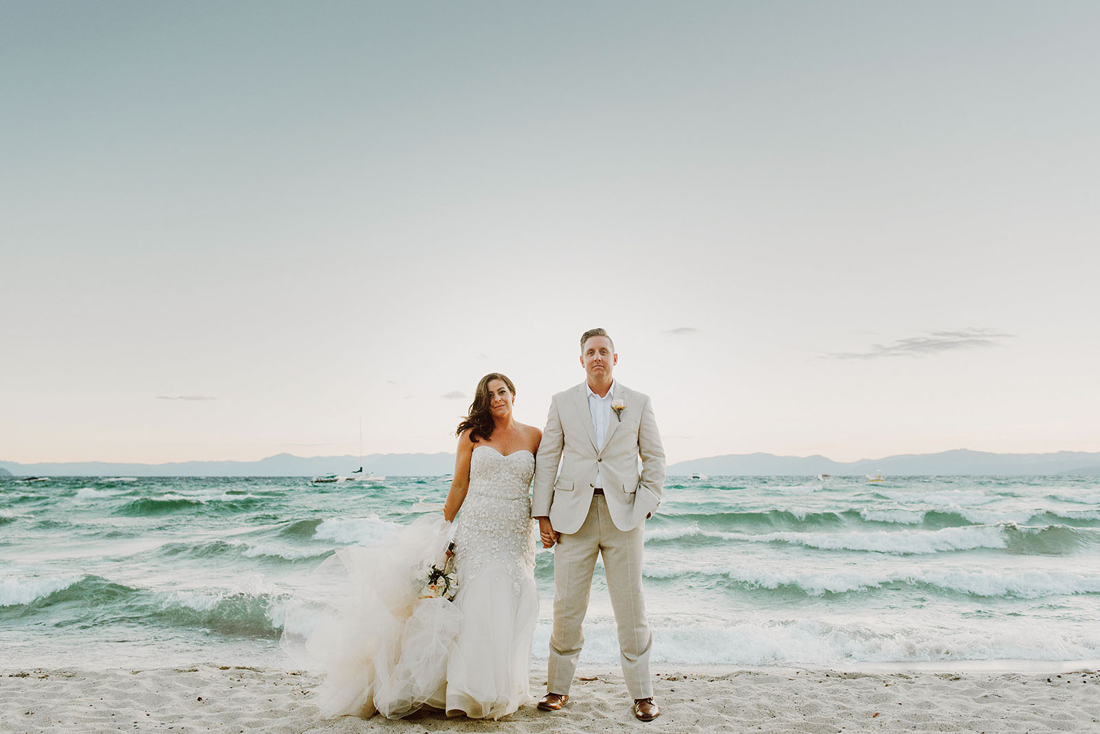 Waves crashing behind Bride and Groom at an Incline Village wedding