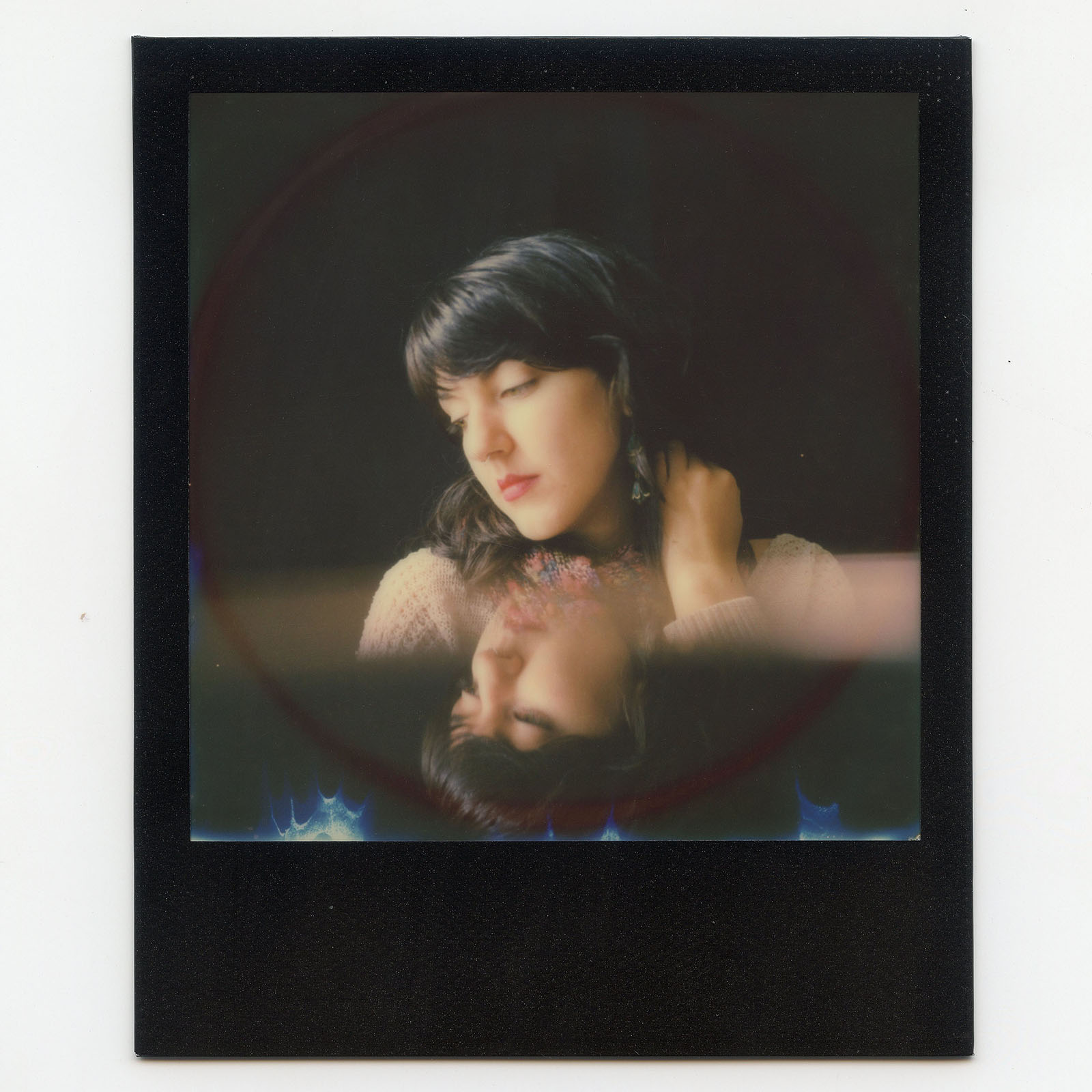 Polaroid portrait of a woman with her reflection