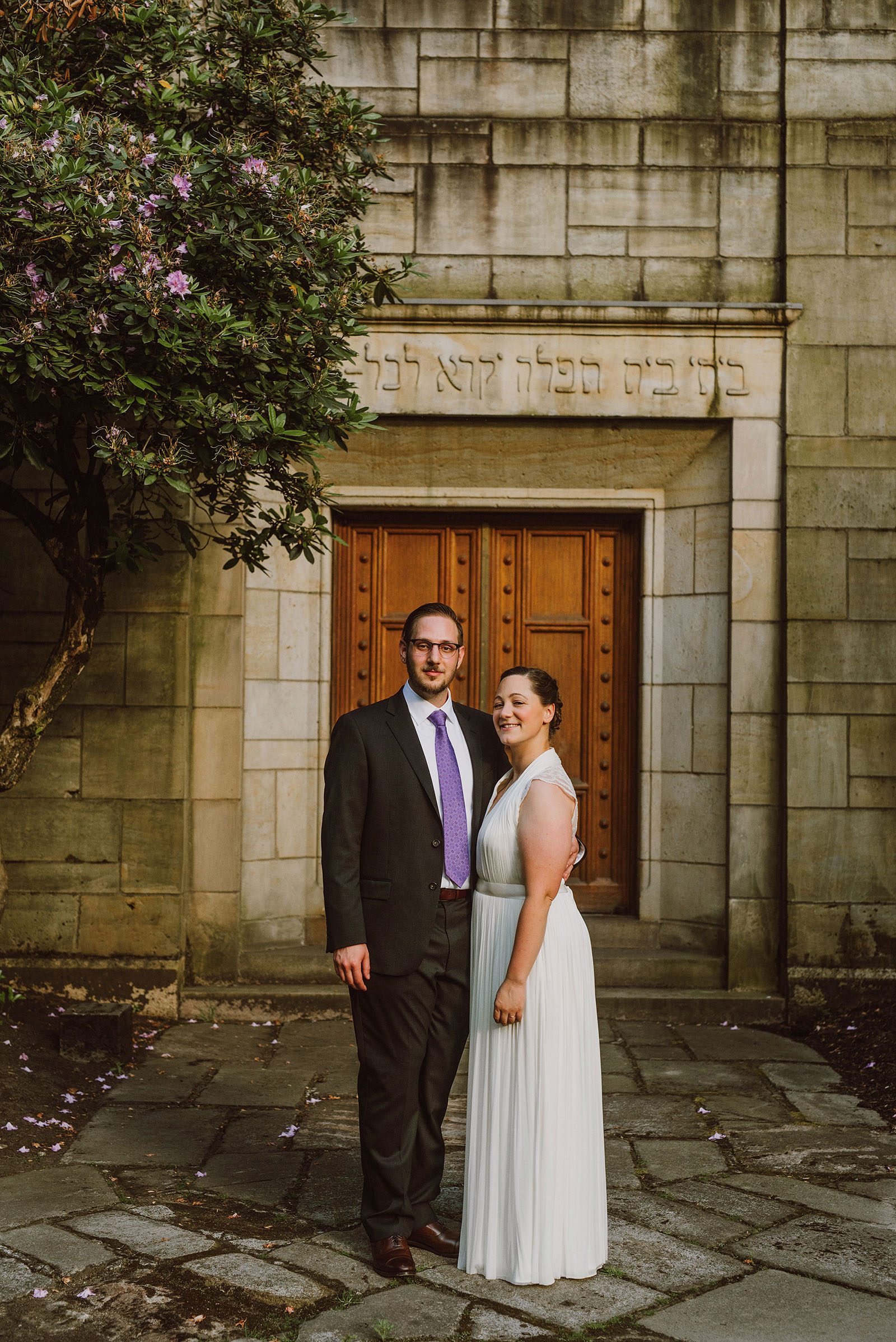 Bride and Groom posing in front of their Congregation Beth Israel wedding in Portland, OR