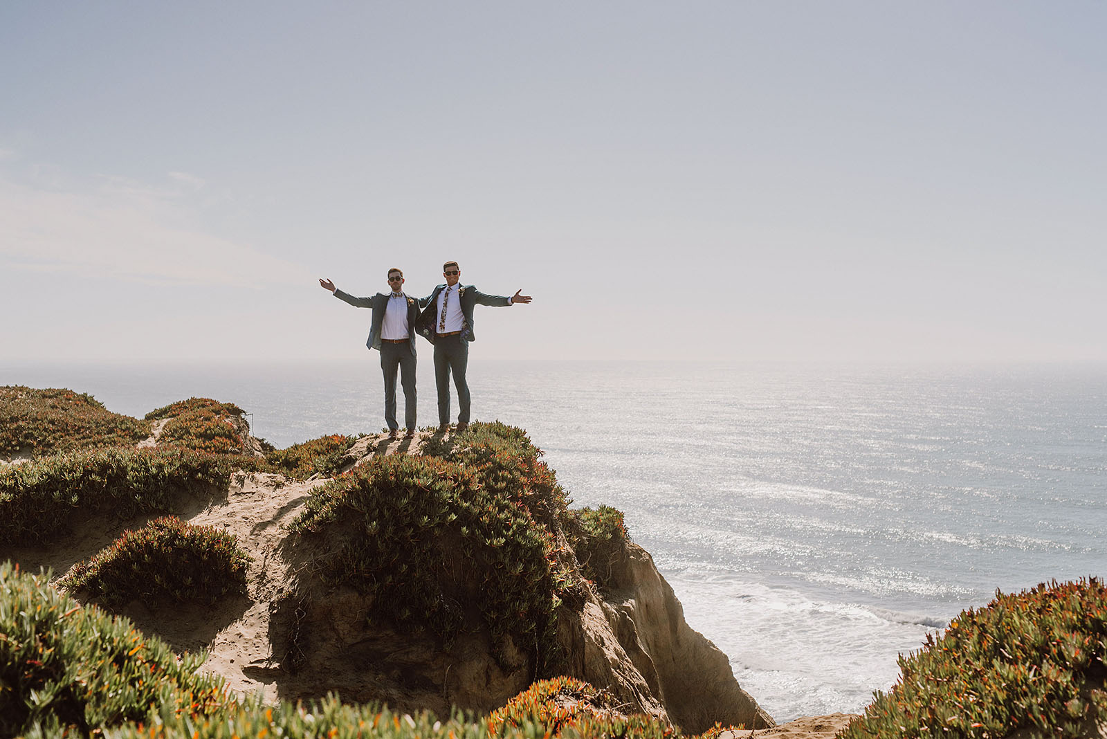 Grooms waving their arms at the San Francisco beach - Foreign Cinema Wedding