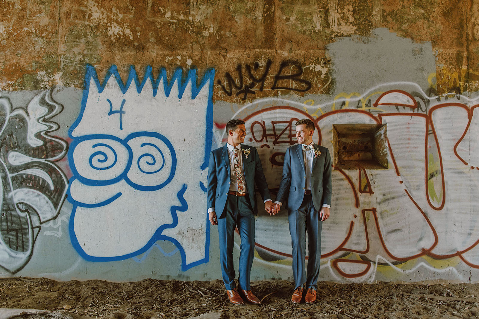 Grooms leaning against a graffiti wall at Fort Funston - Foreign Cinema Wedding