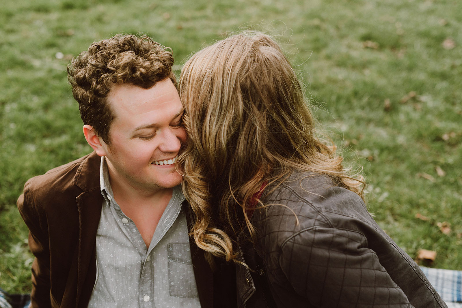 couple snuggling in the grass for their Mt Tabor Engagement Photos