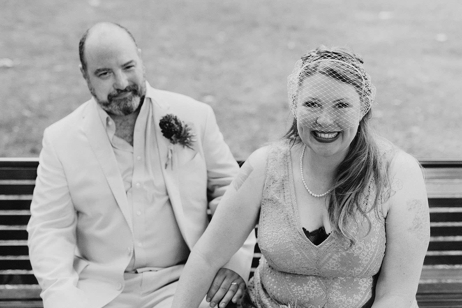 Bride and Groom posing on a park bench at an intimate Ned Ludd wedding